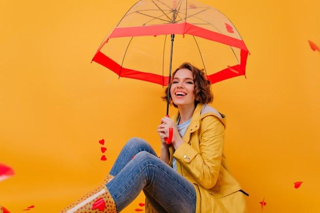 Wspaniała młoda kobieta w dżinsach i żółtym płaszczu pozuje pod parasolem. kryty zdjęcie modnej białej dziewczyny, ciesząc się sesją zdjęciową w jesienny dzień.