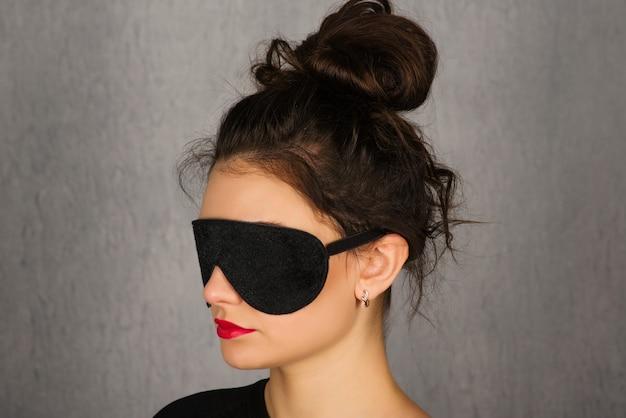 Wspaniała młoda kobieta z czarną maską do spania e