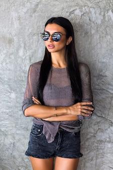 Wspaniała młoda kobieta z długimi włosami brunetki w czarnych stylowych okularach przeciwsłonecznych, szortach i przezroczystej koszulce na szarej ścianie