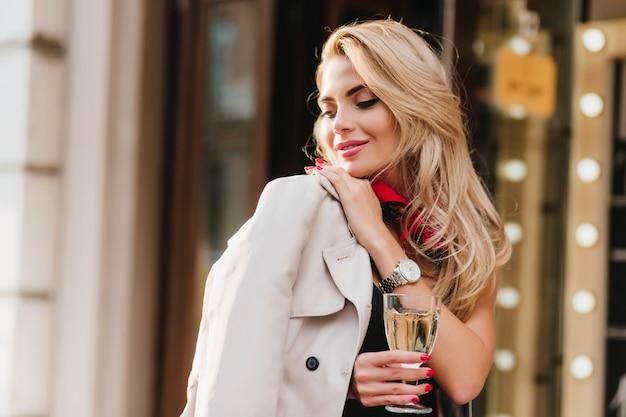 Wspaniała młoda kobieta z elegancką fryzurą, odwracając wzrok i uśmiechając się stojąc. zewnątrz portret zainspirowanej jasnowłosej pani z czerwonym manicure trzymając kieliszek.