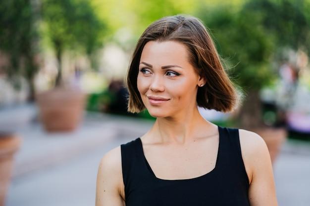 Wspaniała młoda kobieta z krótkimi włosami ubierał przypadkowy patrzeć na boku z ufnością i ładnym uśmiechem chodzi w parku.
