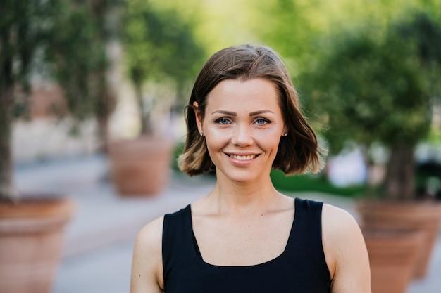 Wspaniała młoda kobieta z krótkimi włosami ubrana na co dzień z pewnością siebie i ładnym uśmiechem na spacerze w parku