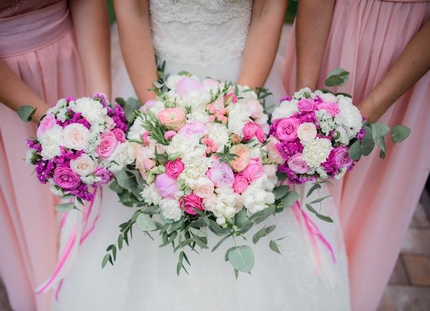 Wspaniała młoda panna młoda i druhny w różowych sukienkach z bukietami ślubnymi w parku