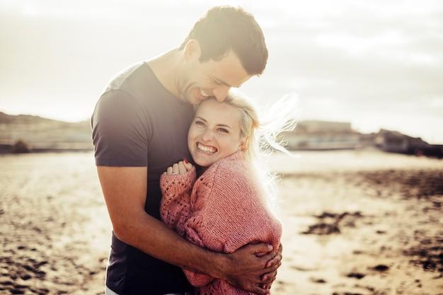 Wspaniała młoda para przytula się i cieszy życiem wraz z naturalnym stylem życia na świeżym powietrzu na plaży latem i zachodem słońca w podświetleniu. blond i czarny kaukaski mężczyzna i kobieta