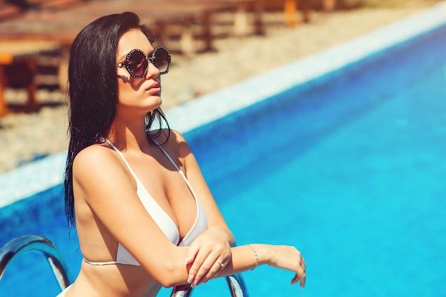 Wspaniała młoda seksowna kobieta pozuje blisko basenu. ładna kobieta w biały strój kąpielowy moda, ciemne okulary, makijaż. rekreacja luksusowy ośrodek zdrowia