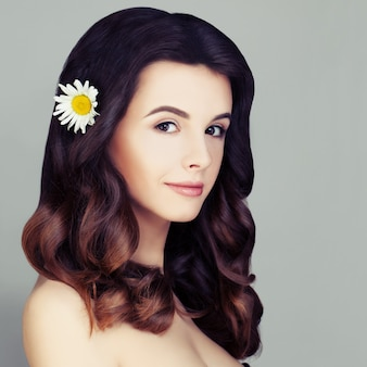 Wspaniała modelka kobieta zdrowe kręcone włosy z farbowaniem włosów ombre i naturalnym makijażem