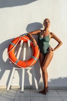 Wspaniała modelka w stroju kąpielowym z kołem ratunkowym.