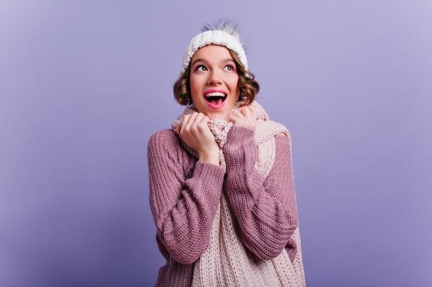 Wspaniała modelka wyrażająca radosne emocje podczas sesji zdjęciowej w zimowych ubraniach. wewnątrz portret ładnej dziewczyny ze stylową fryzurą nosi miękki sweter.
