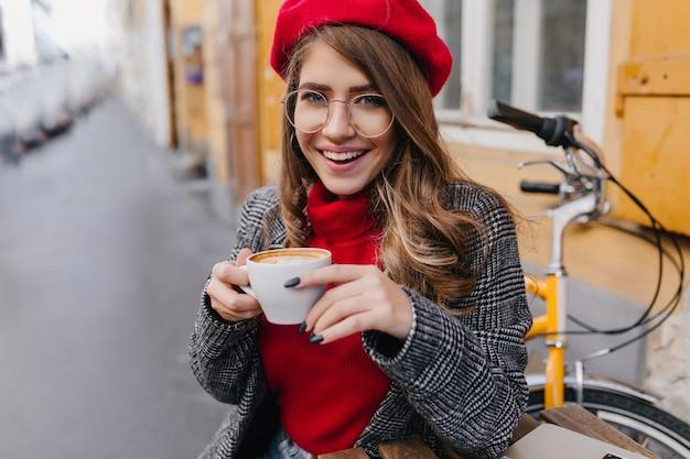 Wspaniała niebieskooka dama we francuskim berecie pije kawę w kawiarni na świeżym powietrzu