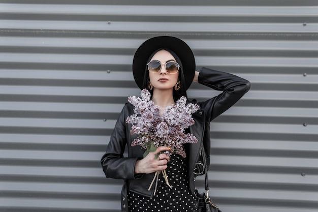 Wspaniała nowoczesna kobieta w modnym kapeluszu w stylowej skórzanej kurtce w okularach przeciwsłonecznych trzyma w ręku bukiet bzu. piękna dziewczyna w czarnych modnych ubraniach pozuje z pięknymi kwiatami na ulicy w mieście