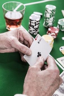 Wspaniała okazja. zbliżenie: mężczyzna trzymający karty siedzący przy stole pokerowym z dużą ilością żetonów i pieniędzy leżących na nim