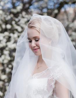 Wspaniała panna młoda blondynka w sukni ślubnej w parku. romantyczna szczęśliwa dziewczyna w sukni ślubnej uśmiechnięta ma ostateczne przygotowania do ślubu