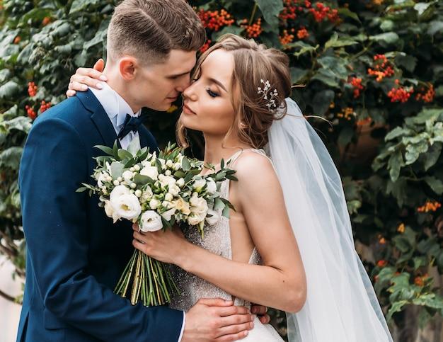 Wspaniała panna młoda i stylowy pan młody delikatnie przytulają i uśmiechają się. para zmysłowy ślub. romantyczne chwile nowożeńców.