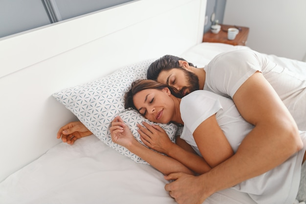Wspaniała para śpi w sypialni. mężczyzna przytula swoją kochającą żonę. poranny czas.