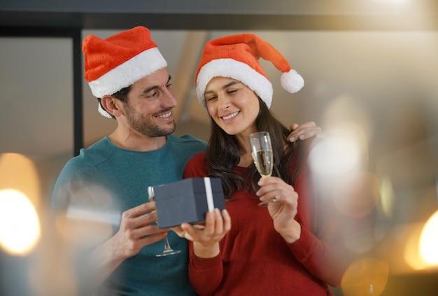Wspaniała para świętuje boże narodzenie w domu z szampanem i prezentami