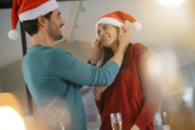 Wspaniała para świętuje boże narodzenie w domu z szampanem i santa kapelusze