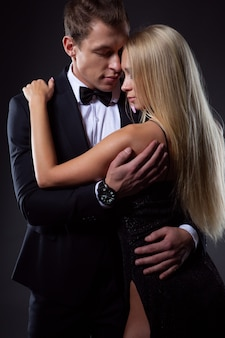 Wspaniała para zakochanych w stylowych sukniach wieczorowych w czułym uścisku