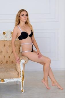 Wspaniała piękna młoda kobieta w koronkowej bieliźnie stojącej, siedzącej i kłaść na kanapie w domu