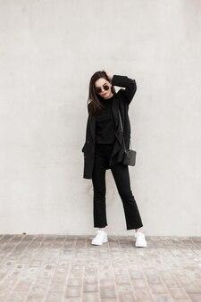 Wspaniała piękna młoda kobieta w modnych okularach przeciwsłonecznych w fajnych czarnych ubraniach młodzieżowych z torebką w białych trampkach pozowanie w pobliżu ściany w mieście. atrakcyjna moda dziewczyna. odzież młodzieżowa dla kobiet.