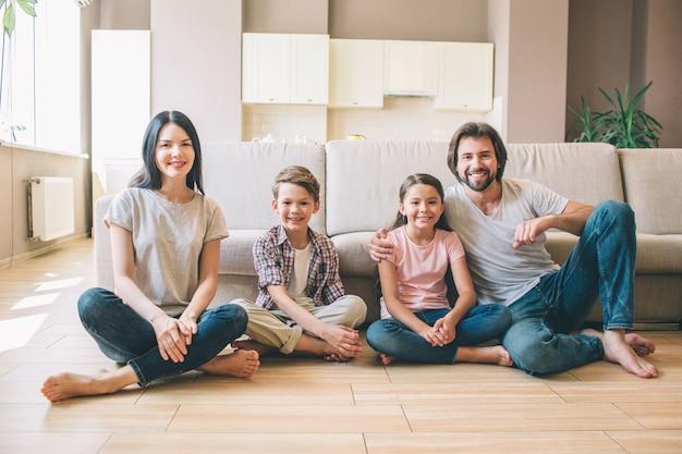 Wspaniała rodzina siedzi na podłodze z nogami pokutymi rękami i patrzy przed kamerą