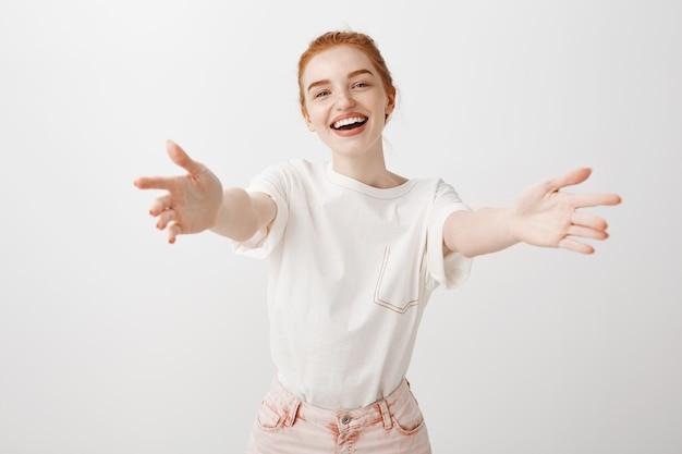 Wspaniała ruda dziewczyna sięgająca rękami do uścisku