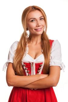 Wspaniała seksowna czerwona z włosami kobieta ono uśmiecha się kamera z tradycyjną bawarską suknią ono uśmiecha się z jej rękami krzyżował odosobnionego na bielu. oszałamiająca kelnerka oktoberfest