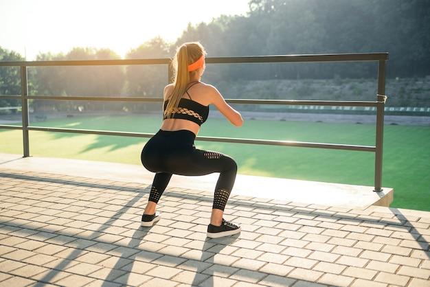 Wspaniała sportowa dziewczyna w czarnej odzieży sportowej i pomarańczowej opasce, która kuca podczas treningu fitness na stadionie na zewnątrz.