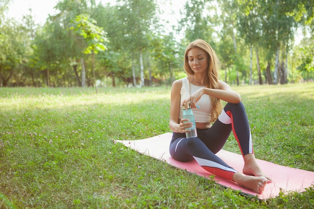 Wspaniała sportowa kobieta robi joga przy parkiem