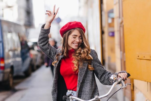 Wspaniała stylowa dziewczyna w czerwonym swetrze wyrażająca prawdziwe emocje siedzi na rowerze