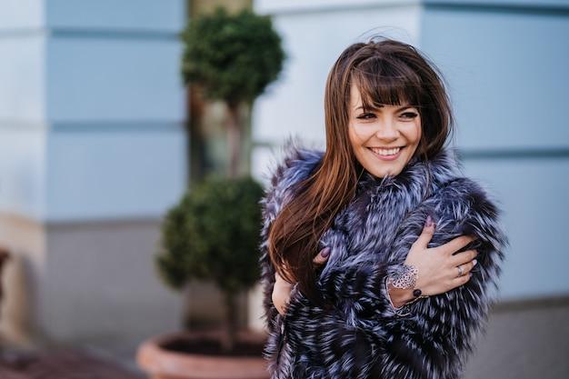 Wspaniała uśmiechnięta brunetka z długimi prostymi włosami ubrana w futro, przytula się i uśmiecha na tle drzew ozdobnych i niebieskiego budynku