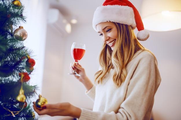 Wspaniała uśmiechnięta caucasian blondynki kobieta z santa kapeluszem na macanie ornamentu na choince i pić wino podczas gdy stojący w żywym pokoju.