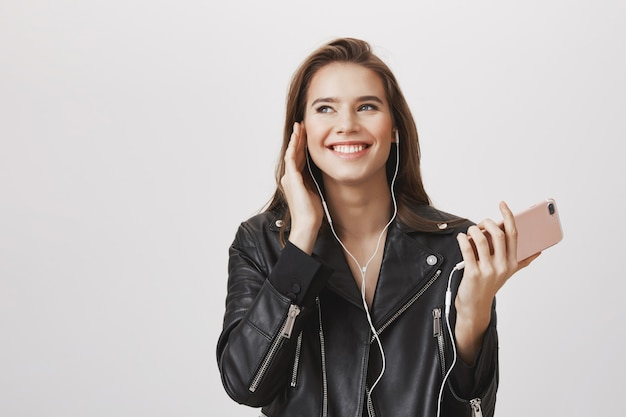 Wspaniała uśmiechnięta kobieta słuchania muzyki w słuchawkach