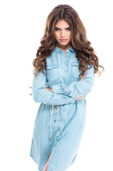 Wspaniała uwodzicielska młoda kobieta z pięknymi kręconymi włosami stojąca z rękami skrzyżowanymi na białej ścianie