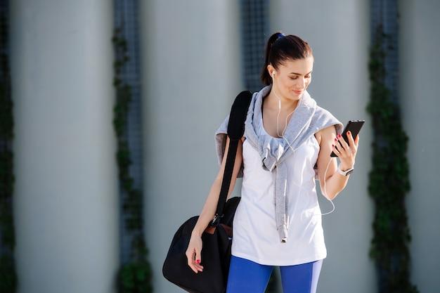 Wspaniała wysportowana kobieta w sportowym stroju patrząca na swojego smartfona