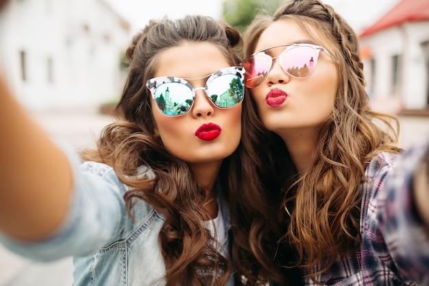 Wspaniałe brunetki z fryzurą, lustrzanymi okularami przeciwsłonecznymi i czerwonymi ustami robiąc selfie z twarzą kaczki.