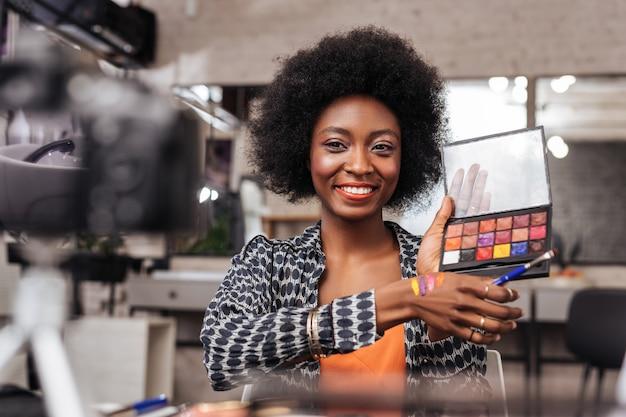 Wspaniałe kolory. piękna ciemnoskóra kobieta ubrana w złotą bransoletkę, demonstrująca publiczności nową paletę