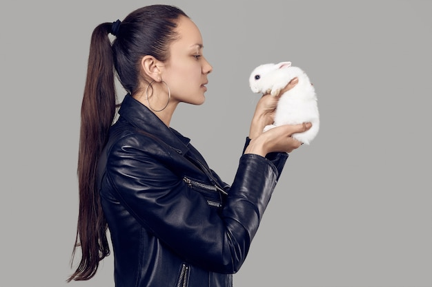 Wspaniałe latynoskie kobiety w modnej skórzanej kurtce z uroczym małym królikiem