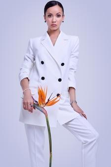 Wspaniałe latynoskie kobiety w modnym białym garniturze z egzotycznym kwiatem