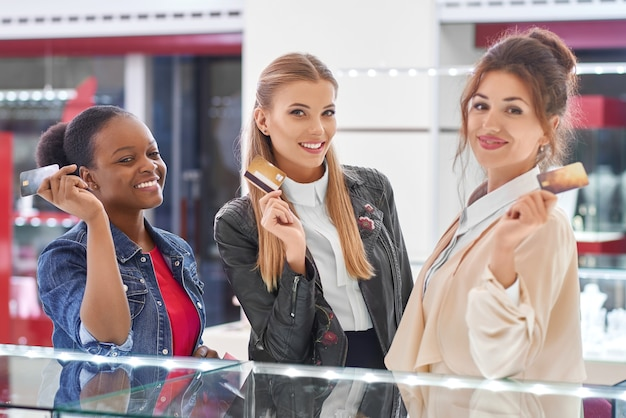 Wspaniałe młode kobiety uśmiechnięte, pokazujące swoje karty kredytowe, pozowanie w centrum handlowym