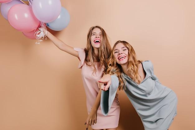 Wspaniałe śmiejące się kobiety trzymające balony z zamkniętymi oczami