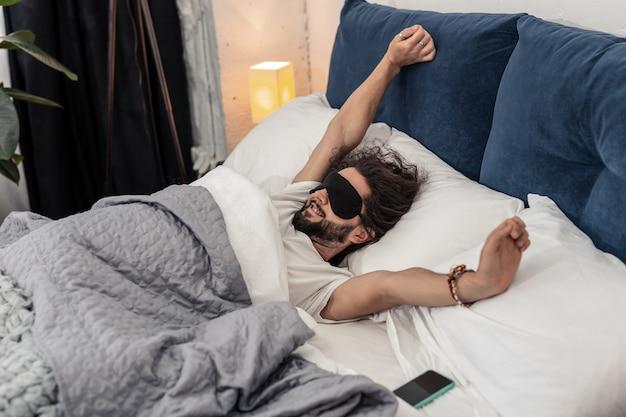 Wspaniałe uczucie. pozytywny miły człowiek rozciągający się rano podczas przebudzenia