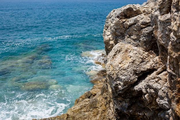 Wspaniałe widoki na błękitne morze śródziemne. słoneczne skały, fale z pianą i bryzgającą wodą. fala uderza w skały na brzegu