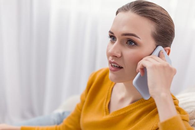 Wspaniałe wieści. zaskoczona energiczna i entuzjastyczna kobieta otwierająca usta podczas korzystania z telefonu i patrząc prosto
