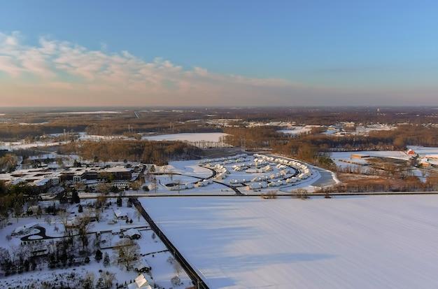 Wspaniałe zimowe krajobrazy dachowe ośnieżone domy pokryte z lotu ptaka z mieszkalnym małym amerykańskim miasteczkiem zaśnieżonym w zimowy dzień po opadach śniegu