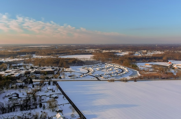 Wspaniałe zimowe krajobrazy dachowe pokryte śniegiem z widokiem z lotu ptaka z miasteczkiem mieszkalnym