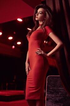 Wspaniałego piękna młoda brunetki kobieta jest ubranym czerwieni suknię