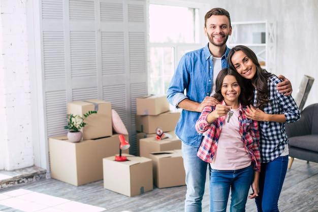 Wspaniali rodzice przytulają swoją nastoletnią córkę, która trzyma klucz do ich nowego mieszkania