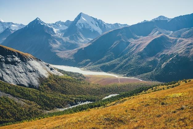 Wspaniały alpejski krajobraz z górskim jeziorem i górską rzeką w dolinie z lasem w jesiennych kolorach na tle ośnieżonych gór sylwetek pod błękitnym niebem. piękna górska dolina jesienią