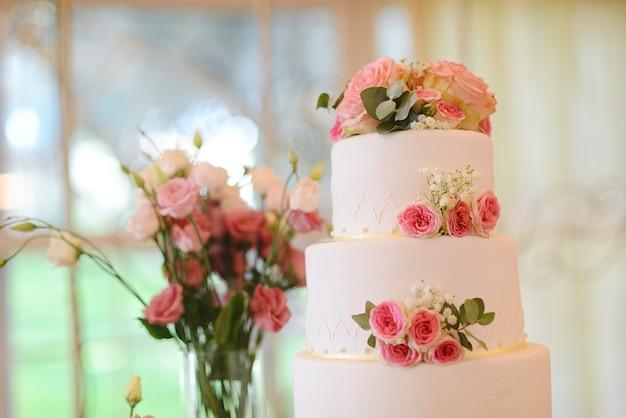 Wspaniały biały tort weselny ze świeżymi kwiatami