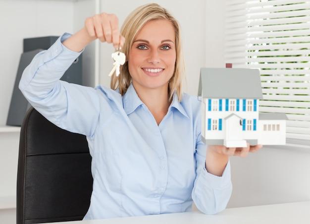 Wspaniały bizneswoman przedstawia modela dom i klucze spojrzenia w kamerę